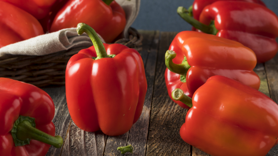 Half a dozen red bell peppers sit on a counter