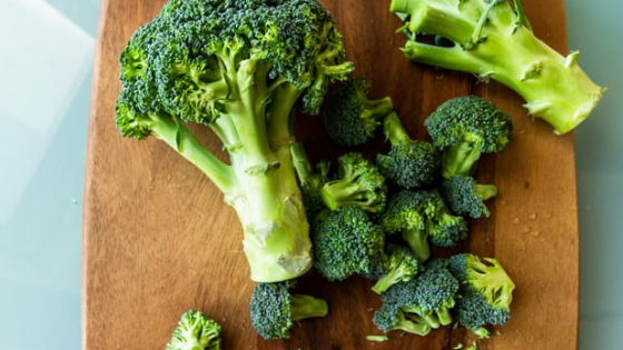 A head of broccoli sits on a cutting board being chopped