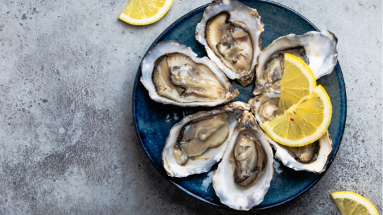 A plate of fresh oysters with lemon wedges sits on a table