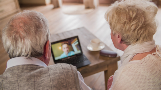 An elderly couple is seen having a video call on their computer
