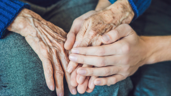 close up of a young person holding hands with an elderly family member