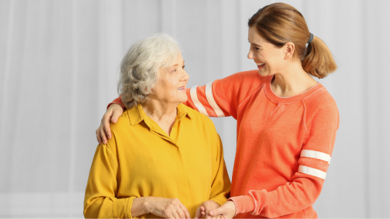 An elderly woman in a yellow shirt smiles walking with a young woman caregiver in orange