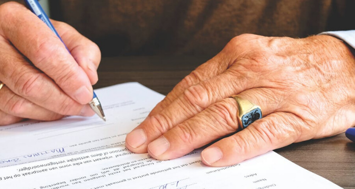 A married man is seen signing a legal document