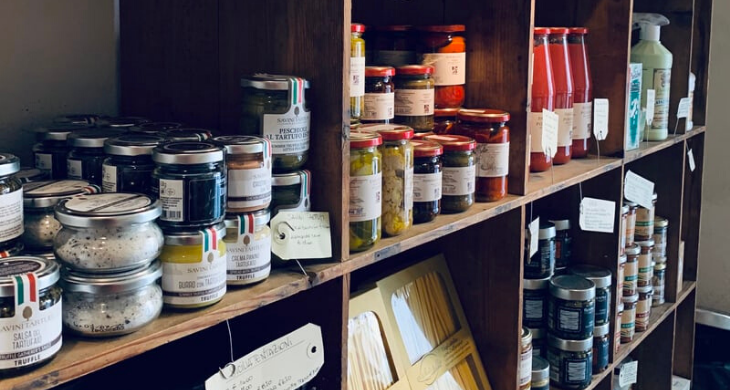 Shelves filled with pantry staples like pickles, pasta and sauces