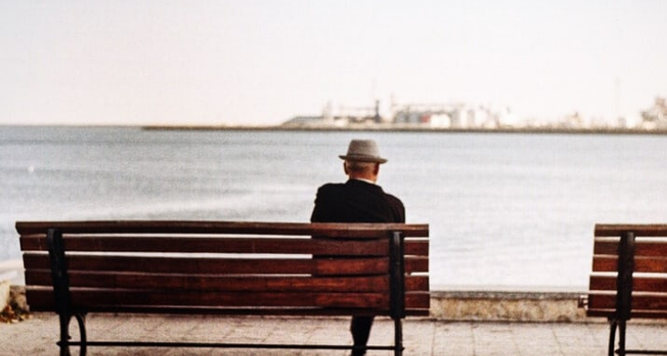 Older gentleman sitting on a bench overlooking the water