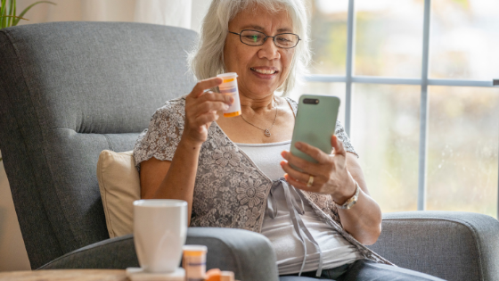 A senior woman shows her prescription bottle to her doctor on a telehealth visit using her smartphone