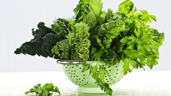A mint green colander overflows with leafy greens