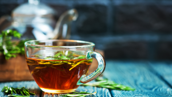 A cup of rosemary tea sits in a clear teacup with a clear teapot in the background