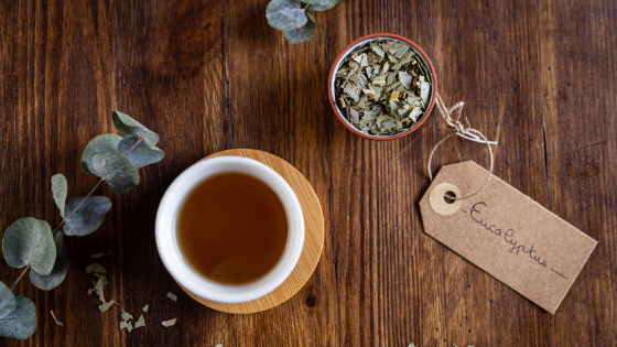 A cup of eucalyptus tea sits on a counter next to dried eucalyptus leaves and a brown tag that reads 'eucalyptus'