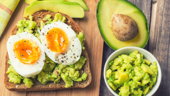 A halved avocado sits next to a plate of avocado toast and a bowl of guacamole