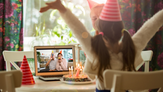 A young girl celebrates her birthday with a cake while video chatting with grandparents from afar