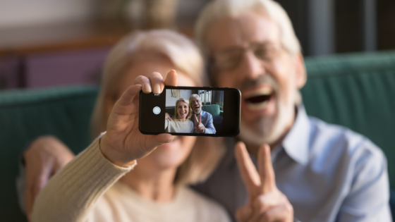 An elderly couple are seen taking a selfie signing the peace sign