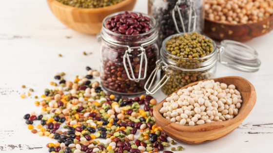 Multiple types and colors of beans and lentils spill out of jars and bowls