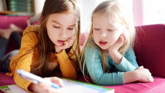 Two young girls are seen writing a letter on the couch