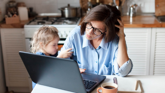 A woman looks stressed staring at her computer with her toddler trying to get attention