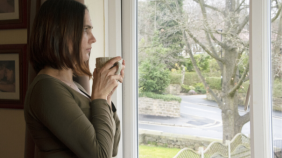 A woman sips coffee while staring out her window