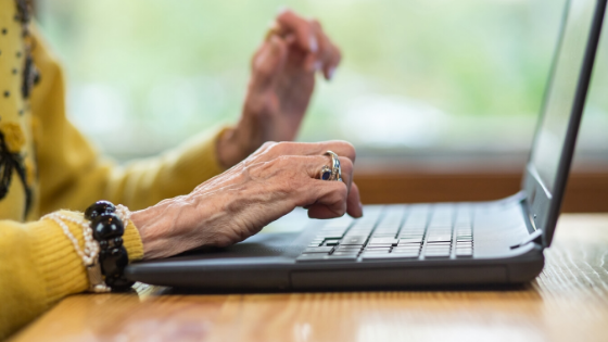 An elderly woman wearing a wedding ring is seen typing on a laptop