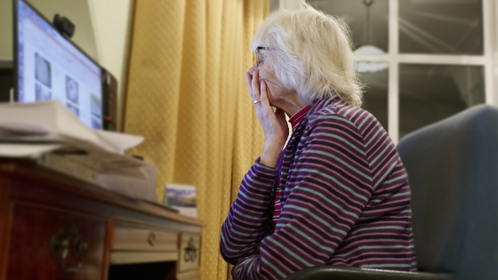 An elderly woman in a striped shirt is seen with her hand covered her mouth & chin in confusion as she sits in front of a computer