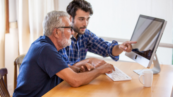 A younger man is seen teaching an older man to use the computer