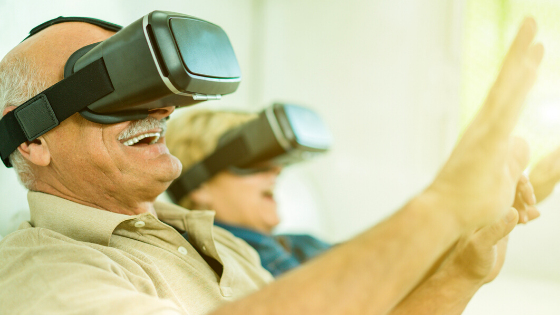 An older couple are seen wearing VR headsets with their arms lifted and their faces smiling