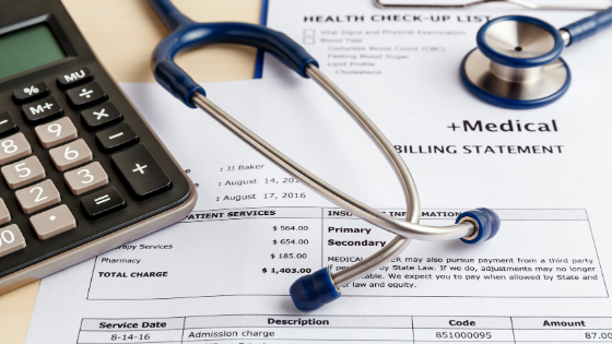 Medical bills on a table next to a calculator and stethoscope