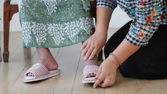 A woman in a plaid shirt is seen putting slippers on a woman in a teal kaftan