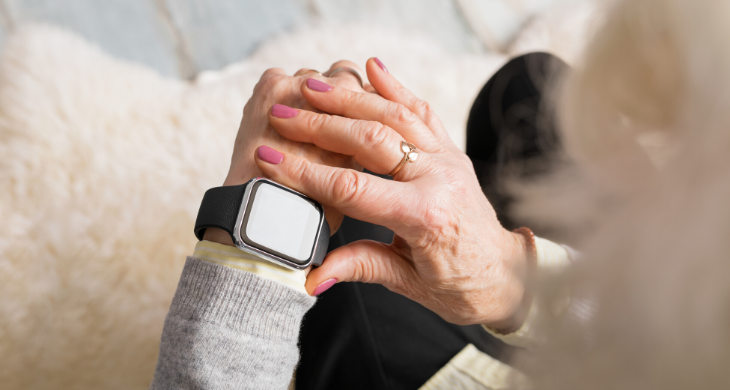 An older woman with pink nail polish is seen looking at her smart watch