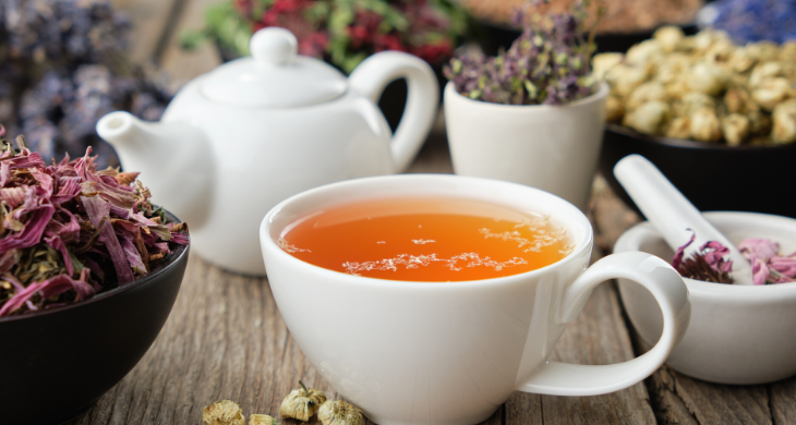 A cup of tea sits on a counter surrounded by bowls of ingredients like ginger, lavender, hibiscus and more