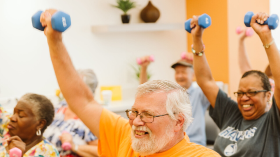 A group of older adults are seen smiling as they work out using hand weights