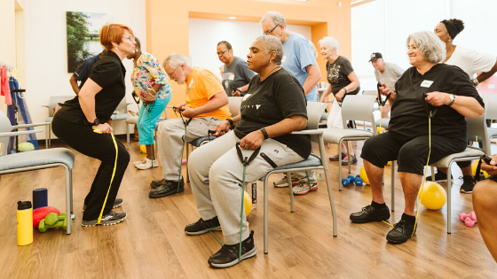 An Iora Primary Care instructor demonstrates leg strength exercises to a class of older adults