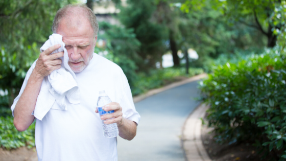An older man is seen walking on a path, sweating and drinking water