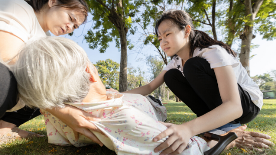 Two younger Asian women attend to an elder woman who has fainted in the park