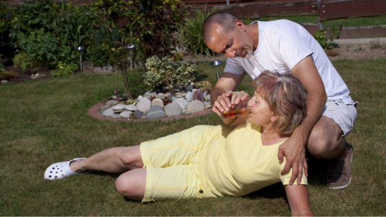 An older man tends to a woman who has heat exhaustion, helping her drink water