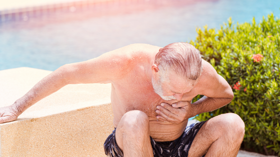 An older man is seen sitting in distress after having climbed out of a pool