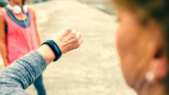 An older woman on a run with a friend stops to check her heart rate