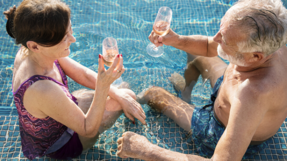 An older couple can be seen sitting in a pool drinking champagne