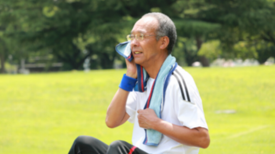 An older Asian man sits in a field using a towel to wipe away sweat