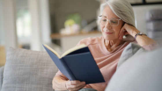 An older woman sits inside reading a book