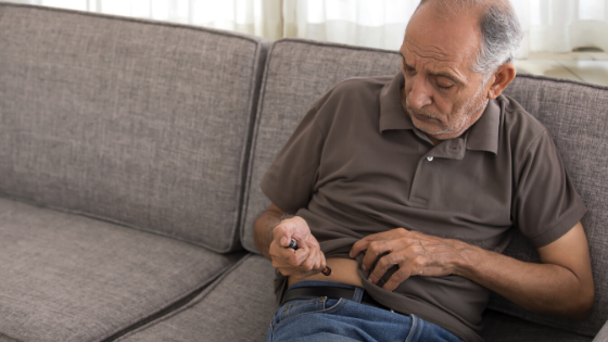 A man sits on his couch while injecting his insulin