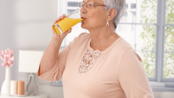 A woman is seen drinking a glass of orange juice