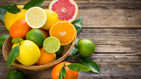 Halved oranges, pink grapefruit, lemons and limes sit in a bowl on a counter