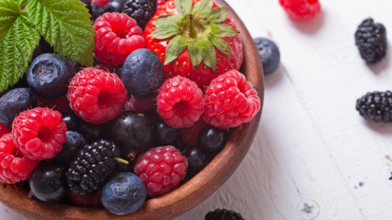 A bowl overflows with fresh blueberries, raspberries, blackberries and strawberries