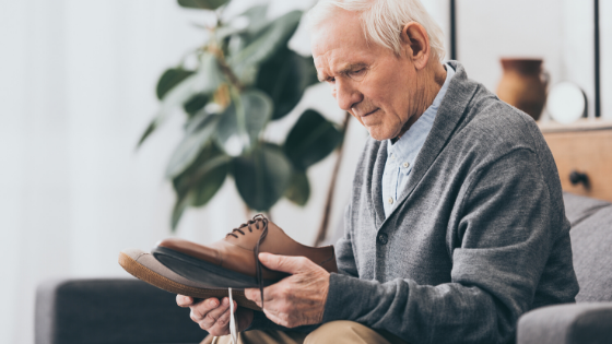 Elderly man is seen staring at two different shoes, looking confused