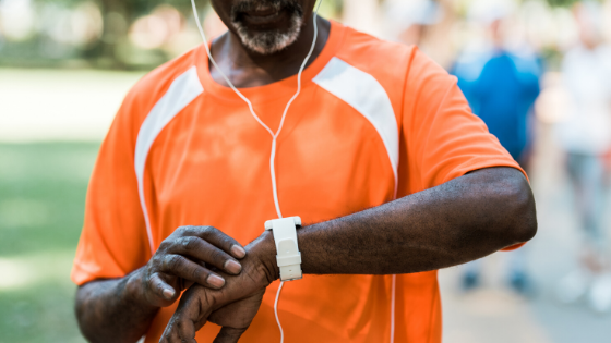 A close up of a man checking his miles on his smart watch while running in the park