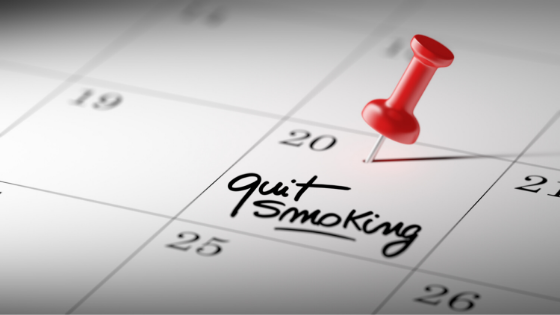 A red thumbtack pierces a calendar with 'quit smoking' written on the 20th of the month