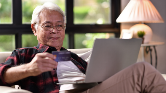 An older man sits on his couch using his credit card for online shopping