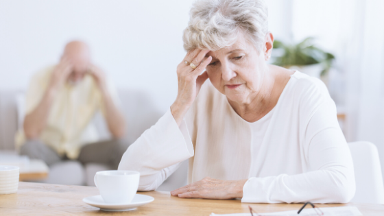 An older woman sits at a table with coffee looking distraught, with a man in the background with his head in his hands