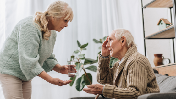 An older woman hands a confused elderly man a glass of water