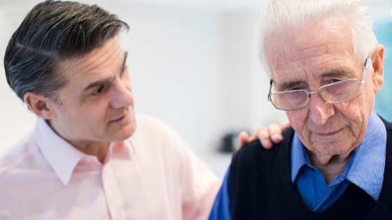 An adult male comforts an confused looking older man with glasses