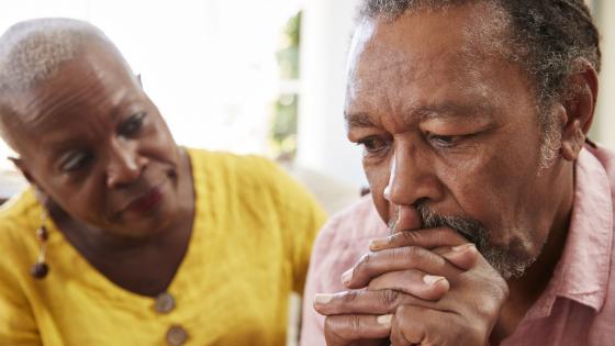 Elder woman stays calm sitting next to elder man who is upset